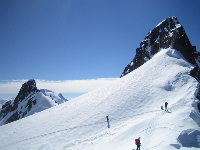 Skiers arrive at Pioneer Pass near overhanging cornices below the East Face of Pioneer Peak.